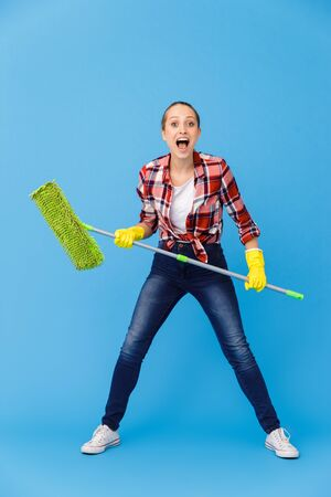 Full length image of content housewife in rubber gloves holding mop and washing the floor while doing housework isolated over blue background Stock fotó