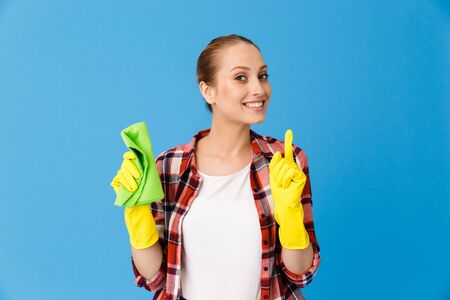 Portrait of cheerful housewife in yellow rubber gloves holding detergent sprayer and cleaning rag while doing housework isolated over blue background Stock fotó
