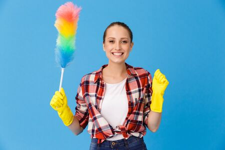 Portrait of happy housewife wearing yellow rubber gloves holding colorful duster while doing housework and cleaning room isolated over blue background