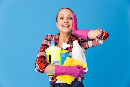 Portrait of happy housewife in rubber gloves holding detergent bottles and washing cleansers while doing housework isolated over blue background