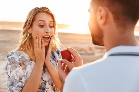 Photo of unshaven man making proposal to his amazed woman with ring in gift box while walking on sunny beach
