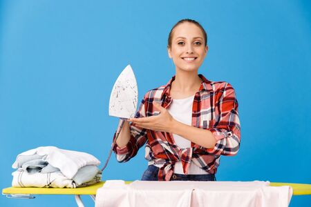Portrait of cheerful housewife wearing casual plaid shirt ironing clean clothes on board while doing housework isolated over blue background