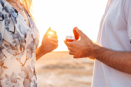 Cropped photo of romantic man making proposal to his girlfriend with ring in gift box while walking on sunny beach