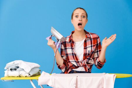 Portrait of excited housewife wearing casual plaid shirt ironing clean clothes on board while doing housework isolated over blue background