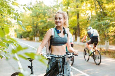 Fröhliches junges Fitnessmädchen, das Rucksack trägt und Sportkleidung trägt, die mit dem Fahrrad im Park spazieren geht? Standard-Bild