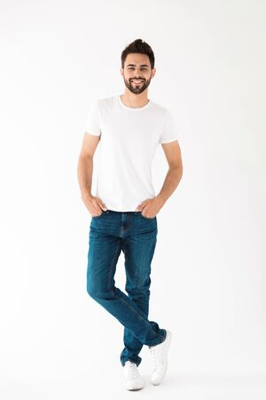 Full length portrait of an attractive young bearded man wearing casual clothing standing isolated over white background, looking at camera