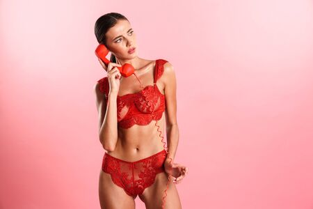 Image of puzzled beautiful woman wearing red sexual lace lingerie talking on retro phone isolated over pink background