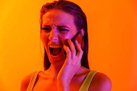 Image of annoyed young woman wearing formfitting sportswear screaming while talking on smartphone isolated over orange neon wall