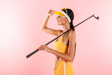 Image of happy pretty woman wearing visor hat smiling and holding golf club isolated over pink background