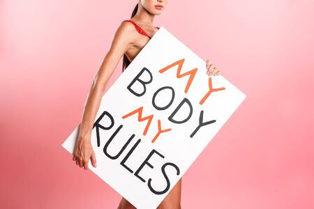 Image cropped of nice serious woman wearing white sexual lace lingerie holding placard with text isolated over pink background