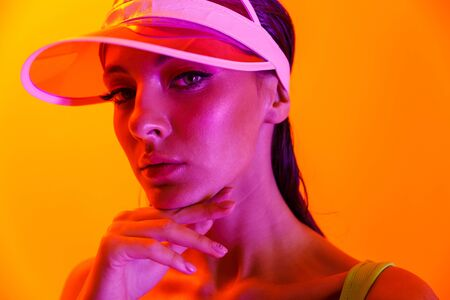 Image closeup of beautiful brunette woman wearing sun visor cap and sportswear posing at camera isolated over orange neon wall