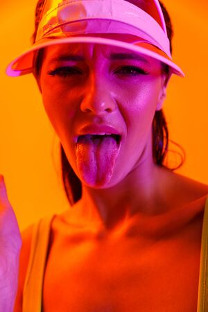 Image closeup of dissatisfied brunette woman wearing sun visor cap and sportswear showing her tongue at camera isolated over orange neon wall Stockfoto