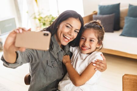 Image of joyful family mother and little daughter hugging and taking selfie photo on cellphone while resting at home in morning