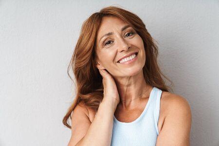 Porträt einer attraktiven lächelnden Frau mittleren Alters, die ein lässiges Outfit trägt, das isoliert über beigefarbenem Hintergrund steht und in die Kamera schaut Standard-Bild