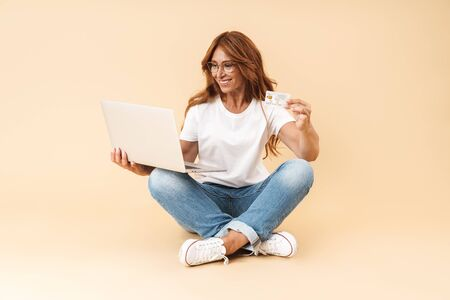 Happy middle aged woman wearing casual outfit sitting on a floor with legs crossed isolated over beige background, showing plastic credit card while using laptop computer Stock Photo
