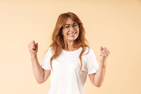 Image of a happy adult mature beautiful woman posing isolated over beige background make winner gesture.