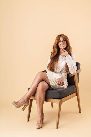 Elegante mujer de mediana edad atractiva feliz sentado en una silla aislada sobre fondo beige