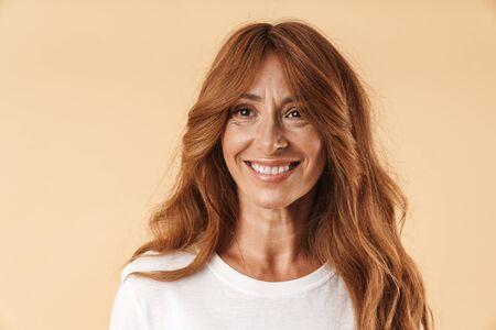 Nahaufnahme des Porträts einer attraktiven lächelnden Frau mittleren Alters, die ein lässiges Outfit trägt, das isoliert über beigefarbenem Hintergrund steht und wegschaut Standard-Bild