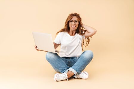 Confused middle aged woman wearing casual outfit sitting on a floor with legs crossed isolated over beige background, working on laptop
