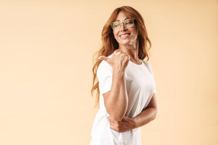 Image of a smiling happy adult mature beautiful woman posing isolated over beige background pointing to copyspace. Stock Photo
