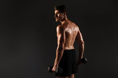 Back view photo of a handsome young strong sportsman posing isolated over black wall background holding dumbbells.