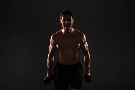 Image of a screaming handsome young strong sportsman posing isolated over black wall background holding dumbbells.