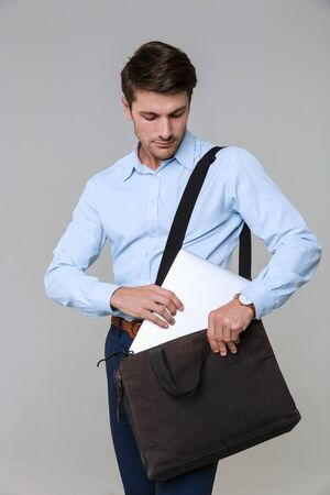 Image of serious businessman in office clothes putting laptop computer in bag isolated over gray background 版權商用圖片
