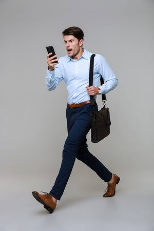 Full length portrait of shocked young businessman walking with smartphone and laptop bag isolated over gray background