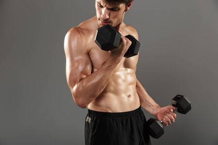 Image of a serious handsome young strong sportsman posing isolated over grey wall background make exercises with dumbbells for arms. Stock fotó