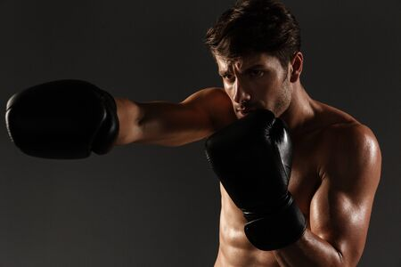 Photo of a concentrated handsome young strong sportsman boxer in gloves make exercises boxing isolated over black wall background.