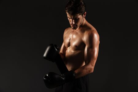 Photo of a attractive strong handsome young sportsman boxer in gloves posing isolated over black wall background. Imagens
