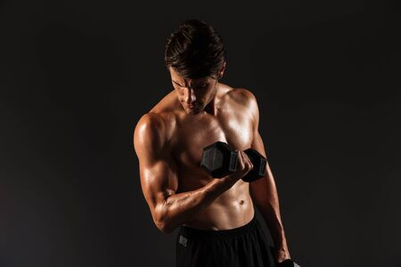 Photo of a serious handsome young strong sportsman posing isolated over black wall background holding dumbbells make exercises for arms.