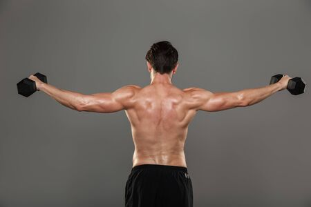 Back view of a handsome young strong sportsman posing isolated over grey wall background make exercises with dumbbells for arms and upper back.
