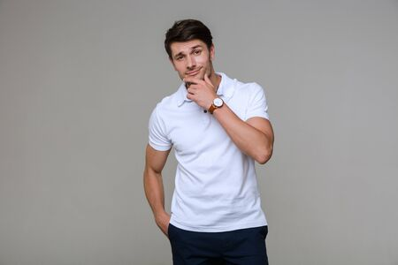 Image of young brunette man wearing basic t-shirt looking at camera and touching his chin isolated over gray background Stok Fotoğraf