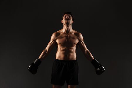 Image of a concentrated strong handsome young sportsman boxer in gloves posing isolated over black wall background.