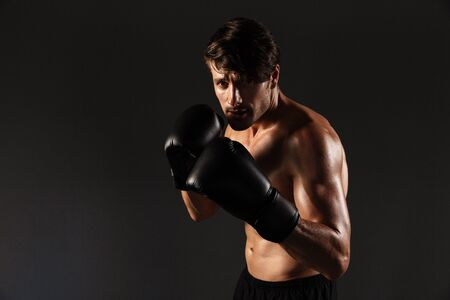 Image of a serious handsome young sportsman boxer in gloves make exercises boxing isolated over black wall background. Imagens