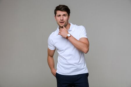 Image of masculine brunette man wearing basic t-shirt looking at camera and touching his chin isolated over gray background