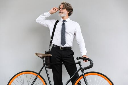 Photo of serious elderly businessman in eyeglasses looking aside while standing with bicycle over gray wall outdoors 写真素材