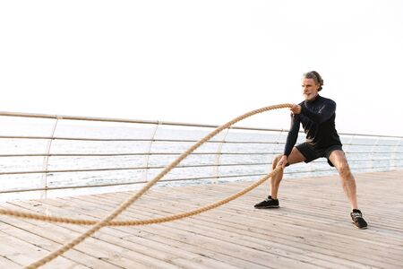 Image of concentrated old man in tracksuit doing exercise with battle ropes while working out near seaside in morning