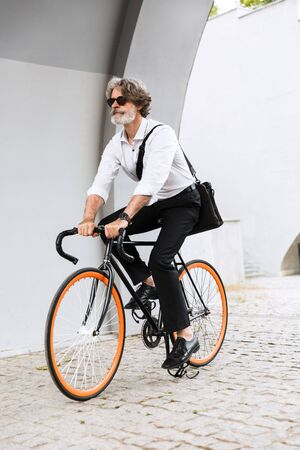 Photo of caucasian elderly businessman in sunglasses and white shirt riding bicycle on city street Reklamní fotografie