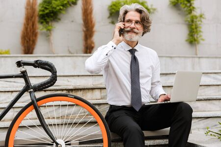 Photo of mature pleased businessman in eyeglasses using cellphone and laptop while sitting on bench with bicycle outdoors 写真素材