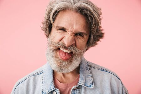 Portrait of amusing old man with gray beard grimacing and sticking out his tongue at camera isolated over pink background