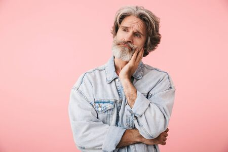 Portrait of sad old man with gray beard looking at copyspace and touching his face isolated over pink background