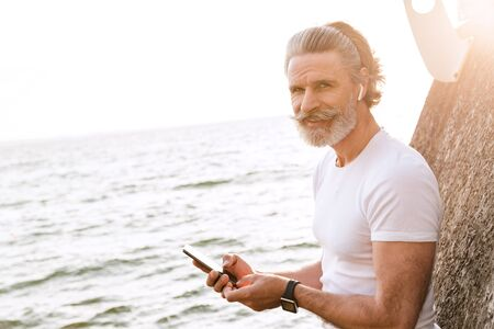 Image of joyful mature man in sportswear using earpod and cellphone while leaning on wall near seaside in morning
