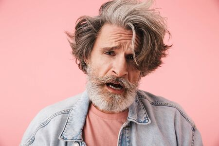 Portrait of puzzled old man with gray beard and messy hair wearing denim jacket looking at camera isolated over pink background