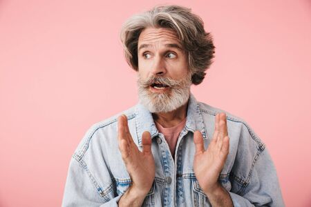 Portrait of astonished old man with gray beard looking aside at copyspace with throwing up hands isolated over pink background
