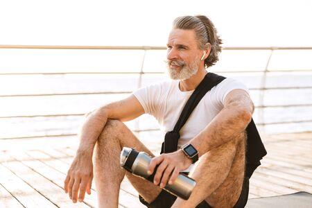 Image of joyful old man in sportswear using earpod and holding water bottle while sitting on mat at boardwalk in morning 写真素材