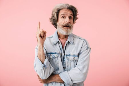 Portrait of surprised old man with gray beard pointing finger upward at copyspace isolated over pink background