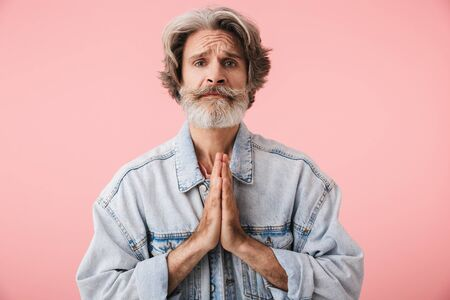 Portrait of upset old man with gray beard looking at camera and praying with palms together isolated over pink background
