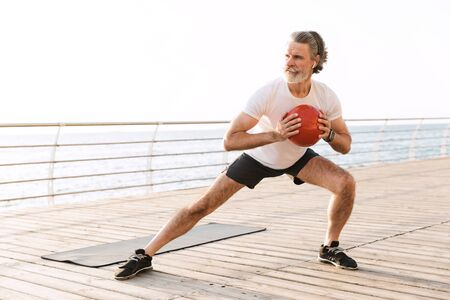 Image of serious old man in sportswear using earpods while doing exercise with medicine ball near seaside in morning